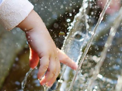 Child running hand through water fountain