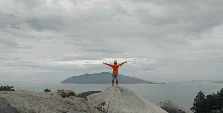 troubled teen standing by the ocean with arms open at a wilderness therapy camp